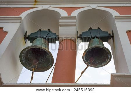 Two Large Rustic Church Bells Above Structure. Building Is Rusty But Paint Is Still In Good Conditio