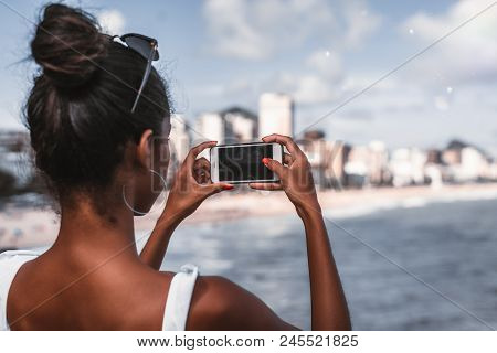 Rear View Of African-american Female With Smartphone Taking A Photo Of The Cityscape And Coastline;