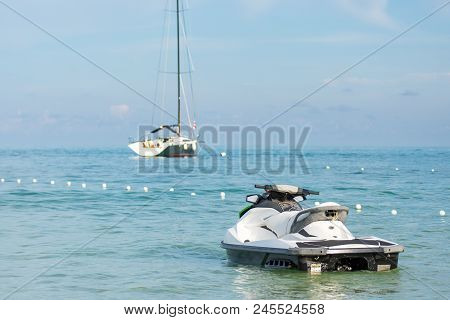 Jetski And Sailboat In The Blue Sea