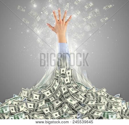 Hand bursting out from a huge money pile