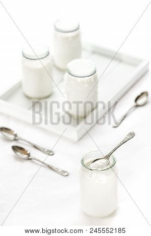 Four Pots Of Homemade Yogurt On White Background