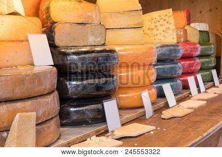 Variety and different types of cheese on stall market shop counter. Lot of stack cheese in store wit