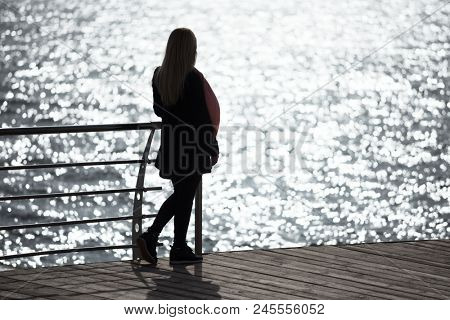 Seascape with sunlight reflecting in the sea. Girl contemplates the dawn