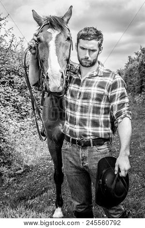Good Looking, Hunky Cowboy With Boots, Chequered Shirt And Hat Stands In Front Of His Stallion, Hors