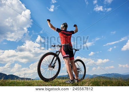 Back View Of Athletic Professional Sportsman Cyclist Standing With Bike On Top Of Hill, Rasing Hands