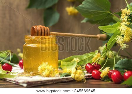 Open Glass Jar Of Liquid Honey And Honey Dipper, Bunch Of Linden Flowers And Red Cherry On Wooden Su