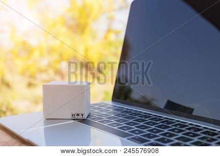 Mini Cardboard Box On Laptop Keyboard With Yellow Nature Background. Consumers Can Buy Products Dire