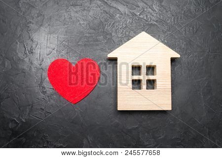Heart And Wooden House On A Gray Concrete Background. The Concept Of A Love Nest, The Search For New