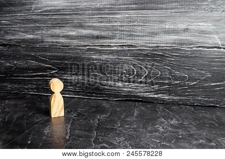 A Lone Wooden Figure Of A Man Stands On A Gray Background. A Lonely Man Stands And Looks. One Person