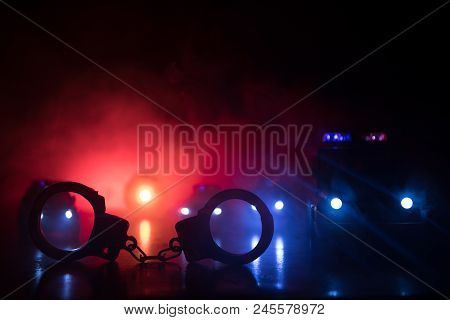 Closed Handcuffs On The Street Pavement At Night With Police Car Lights