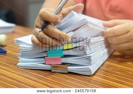 Teacher Hand Holds Pen For Checking Student's Homework Assignment On Table Office. Paper Documents S