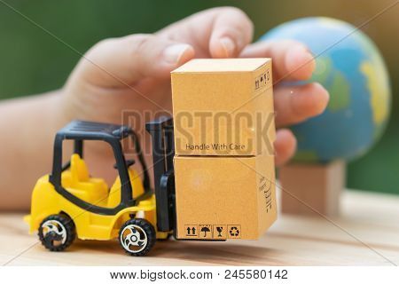Handle Cardboard Boxes On Mini Forklift Trucks With Nature Background And Globe Nearby. Logistics An
