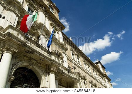 Italian And Eu Flags On A Balcony Of The Italian Army Academy With Blue Sky And White Clouds. Modena