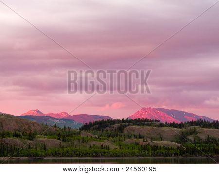 Distant Yukon mountains glowing in sunset light