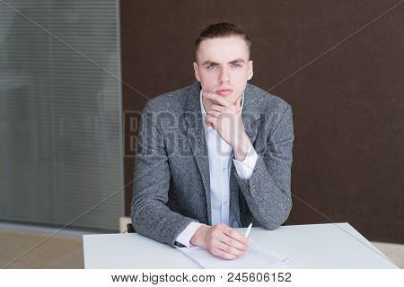 Serious Business Man At Work. Corporate Manager At His Workplace. Thoughtful Pensive Office Worker