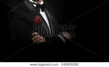 Young Handsome Man In Suit With Bow-tie On Dark Background.