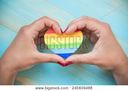 Lgbt  Concept, Hands Holds A Heart Painted Like A Lgbt Flag On Blue Background. Lgbt Symbolic In Hea