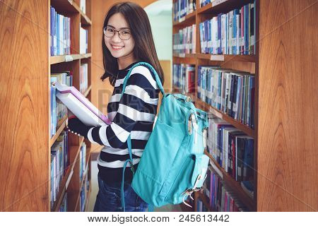 Education First, Beautiful Female College Student Holding Her Books Smiling Happily Standing In Libr