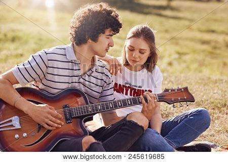 Outdoor View Of Lovely Female And Her Male Companion Have Leisure Time, Handsome Teenager Plays Guit