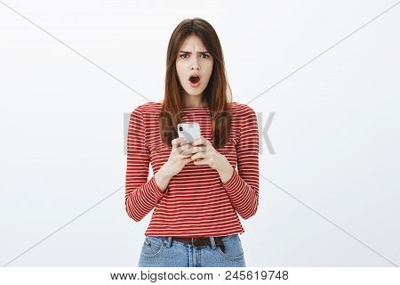 How could you post picture where I look bad. Portrait of displeased complaining young woman in striped blouse, yelling or whining, frowning from dislike, holding smartphone, reading bad news. poster