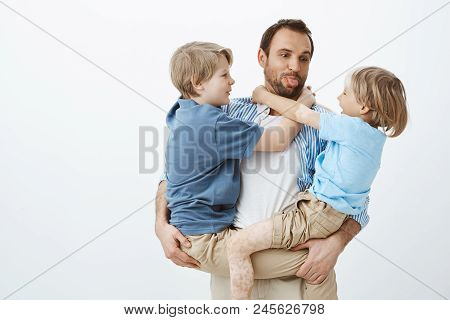 Dad Loves Spending Time With Family. Carefree Happy Father Holding Sons In Arms And Sticking Out Ton