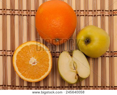 Apples and oranges on a wooden lining