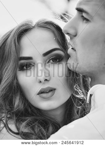 Couple In Love Embraces. Young Newlywed Couple Of Woman In Wedding Dress And Man Embracing In Field