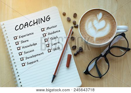 Coaching And Check List Marks In Notebook With Glasses, Pencil And Coffee Cup On Wooden Table. Proje