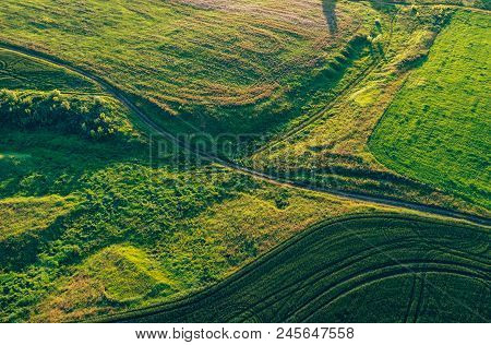 Aerial View From Drone Or Aerostat In Countryside Rural Farmland With Green Field Hills And Meadows,