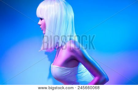 High Fashion model girl in colorful bright sparkles and neon lights posing in studio, portrait of beautiful woman, trendy glowing make-up. White hair, colorful make up. Glitter Vivid neon makeup