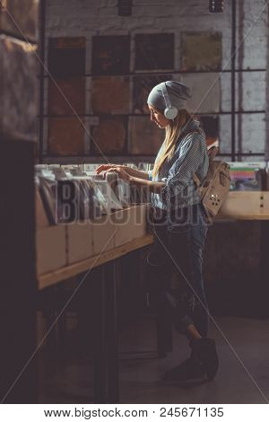 Young attractive girl with headphones browsing records