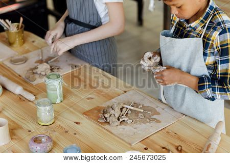 Little boy and his classmates standing by workplace and learning to make clay handcraft