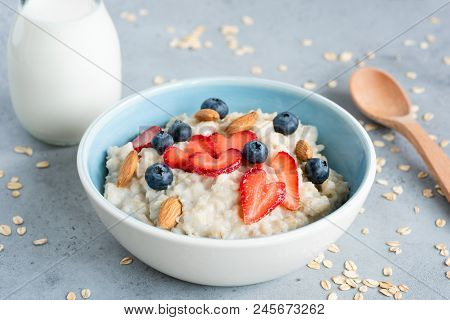 Oatmeal Porridge In A Blue Bowl With Berries And Nuts. Porridge Oats Bowl With Strawberries Blueberr