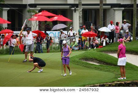 KUALA LUMPUR, MALAYSIA - OCTOBER 16: Aman Blumenherst (black) prepares for her putt on day 4 of the Sime Darby LPGA Malaysia 2011 golf tournament on Oct 16, 2011 in Kuala Lumpur, Malaysia.