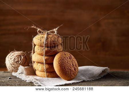 Homemade Cookies Tighted With Piece Of Rope On Homespun Napkin Over Wooden Table, Close-up, Selectiv