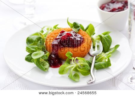 Breaded and deep-fried  camembert with cranberry sauce and corn salad