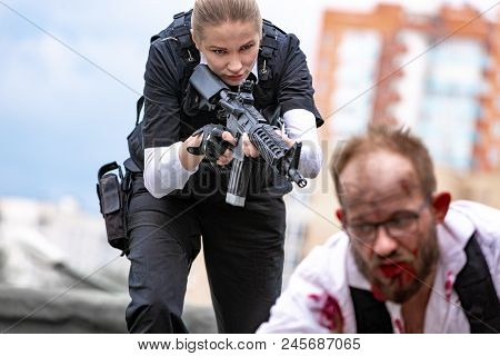 Woman Soldier, Spy Agent Killer Or Police Woman With A Gun In Her Hand Holding At Gunpoint A Man Lyi