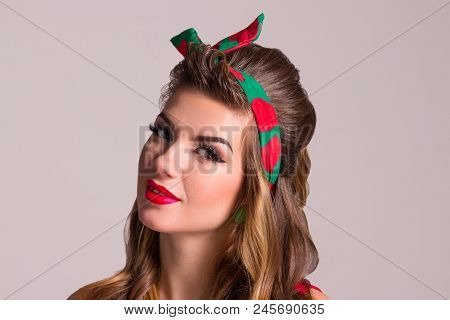 Girl with hairdo and make up poses in studio, pin up style, close up portrait poster