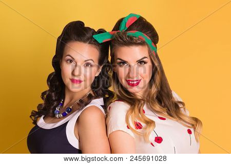 Two Pretty Women In Dresses Pose In Yellow Studio, Pin Up Style
