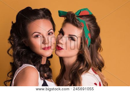 Two Pretty Women In Dresses Pose In Orange Studio, Pin Up Style