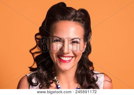 Happy Brunette With Hairdo And Make Up Smiles In Studio, Pin Up Style, Close Up Portrait