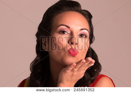 Pretty Brunette With Hairdo Sends Air Kiss In Studio, Pin-up Style, Close-up Portrait