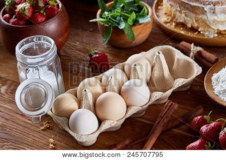 Top View Raw Ingredients For Cooking Strawberry Pie Or Cake On Wooden Table: Eggs, Sugar And Strawbe