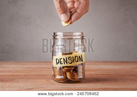 Pension. Glass Jar With Coins And An Inscription Pension. Man Holds  Coin In His Hand.