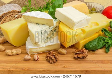 Pieces Of Different Soft And Semi-soft Cheese With Mold, Medium-hard And Hard Cheese Among Of Nuts A