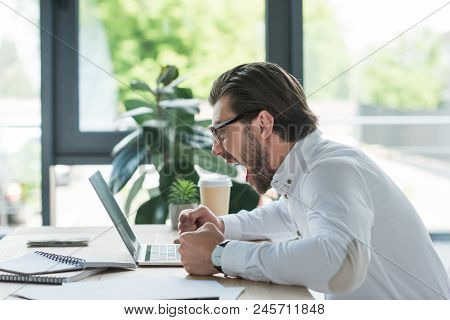 Side View Of Mad Young Businessman Shouting At Laptop In Office
