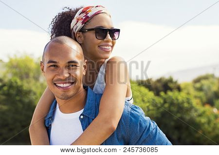 Portrait of young black man holding beautiful woman on back and looking at camera. African american woman with sunglasses enjoying piggyback on boyfriend at park and looking away in a summer holiday.