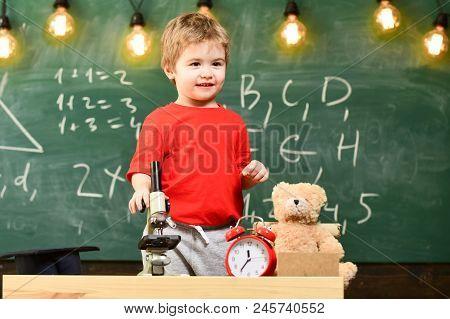 Child, Pupil On Calm Face Near Microscope. Kid Boy Near Microscope In Classroom, Chalkboard On Backg