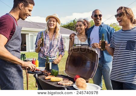 Multiethnic friends at barbecue party in the garden of house. Young man cooking meat on barbeque during summer holiday. Girls and guys having fun and drinking beers around the bbq.