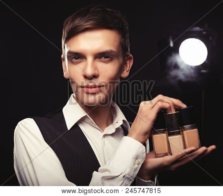 Beauty concept. Young male make up artist posing with foundation for make-up d.